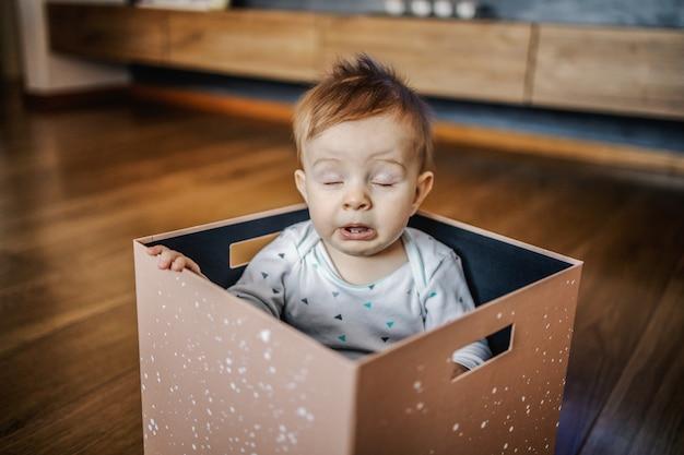 Adorável menino loiro caucasiano sentado na caixa e espirrando. interior da casa. Foto Premium