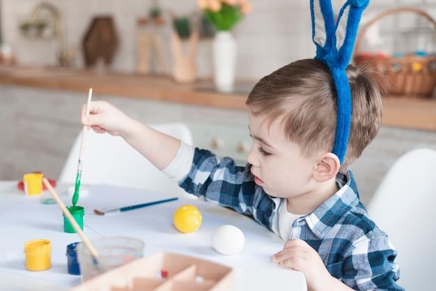Adorável menino pintando ovos de páscoa Foto gratuita