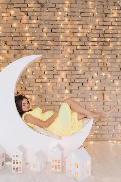 Adorável mulher grávida no vestido amarelo encontra-se na lua antes de uma parede Foto gratuita