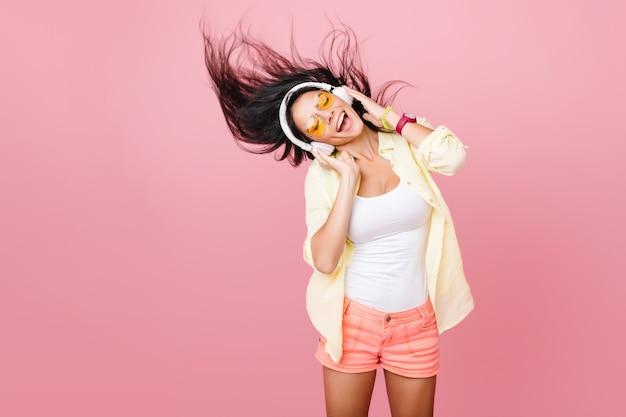 Adorável mulher latina em regata branca dançando com boa música e balançando o cabelo. retrato interior da graciosa menina asiática ativa em shorts rosa relaxantes em fones de ouvido. Foto gratuita