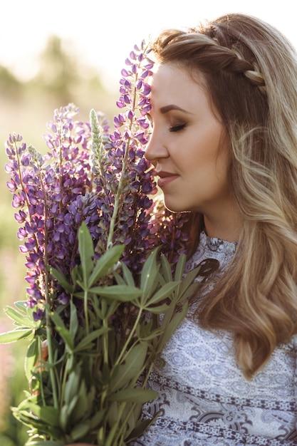 Adorável mulher loira de vestido azul atravessa o campo de flores de lavanda violeta Foto gratuita