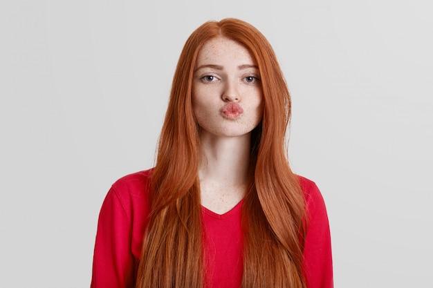 Adorável mulher ruiva com pele sardenta, arredonda os lábios, vai beijar alguém, tem longos cabelos avermelhados, isolados no branco. poses de mulher bonita natural interior. conceito de linguagem corporal Foto gratuita