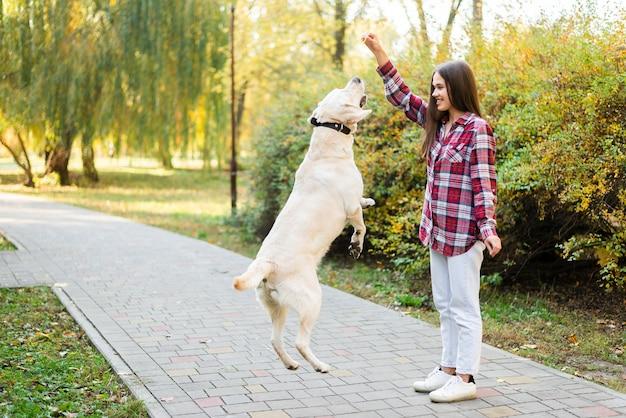Adulta mulher brincando com seu cachorro Foto gratuita