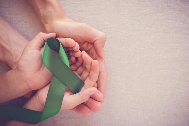 Adulto e criança mãos segurando a fita verde, conscientização do câncer Foto Premium