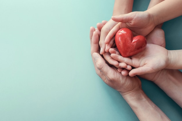 Adulto e criança mãos segurando um coração vermelho no fundo do aqua Foto Premium