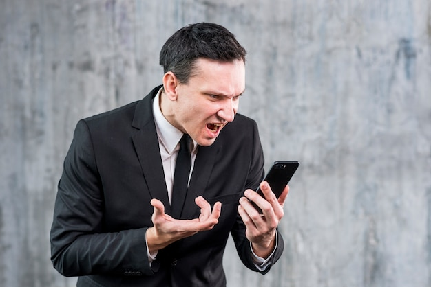 Adulto, homem negócios, obtendo, zangado, e, gritando, telefone Foto gratuita