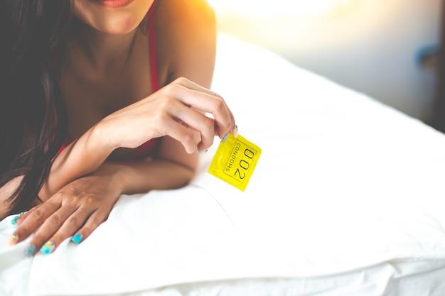 Adulto, mulher sexy, preparar, e, segurando, um, preservativo, em, vermelho escuro, lacy, roupa interior, mulheres, roupa interior, cama Foto Premium