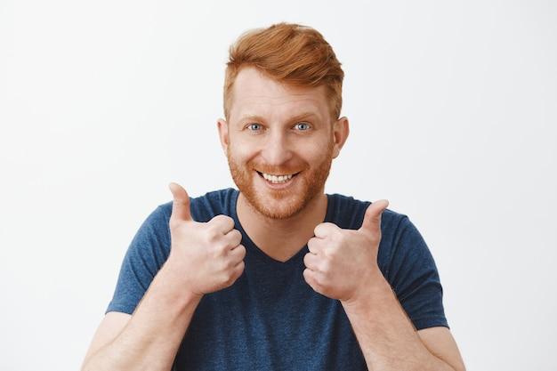 Adulto ruivo atraente e apoiador com cerdas gostando de um ótimo plano levantando as mãos, mostrando os polegares para cima, sorrindo alegremente Foto gratuita