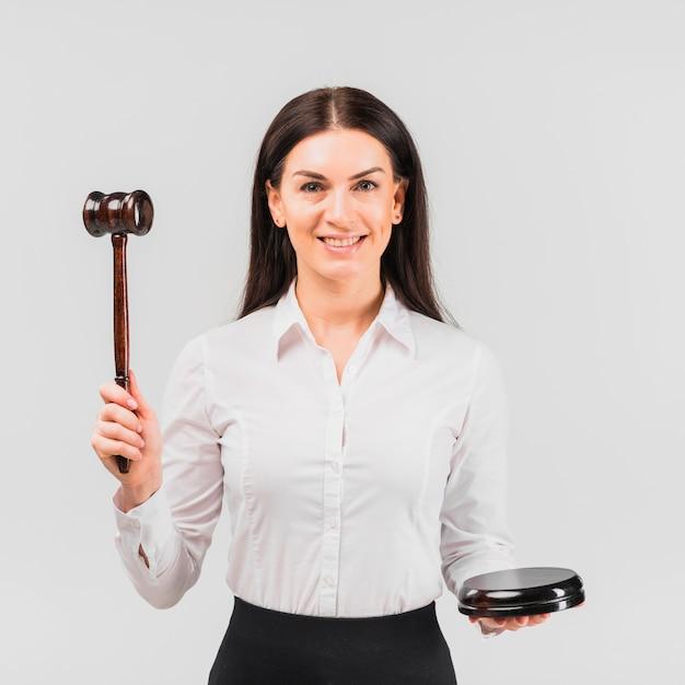 Advogado de mulher em pé com o martelo e sorrindo Foto gratuita