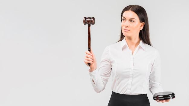 Advogado de mulher em pé com o martelo na mão Foto gratuita