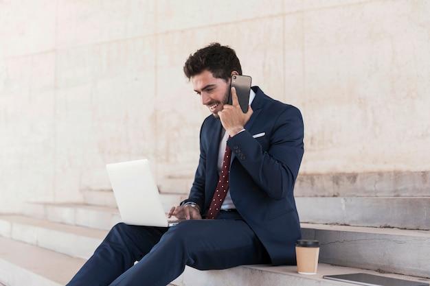 Advogado de vista lateral com laptop falando ao telefone Foto gratuita