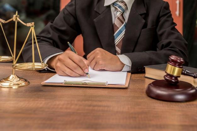 Advogado do advogado do tribunal que trabalha com originais e martelo de madeira no tabel na sala do tribunal. Foto Premium