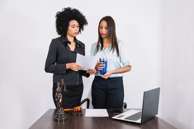 Advogado e assistente de pé à mesa com documentos Foto gratuita