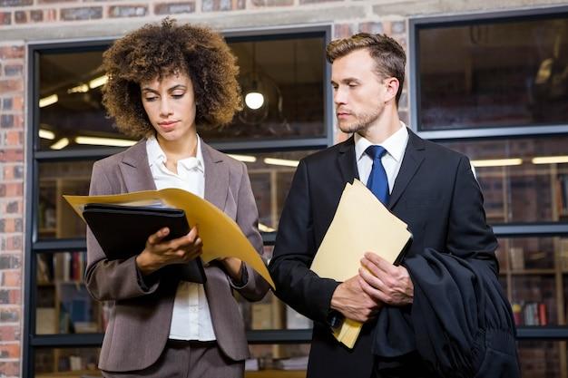 Advogado e empresária olhando documentos no escritório Foto Premium