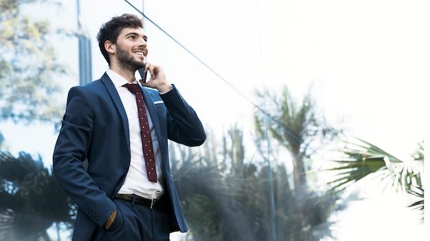 Advogado elegante da vista lateral que fala no telefone Foto gratuita