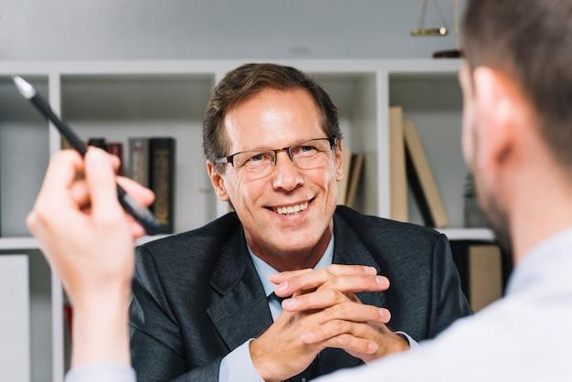 Advogado maduro feliz sentado com cliente de negócios Foto gratuita