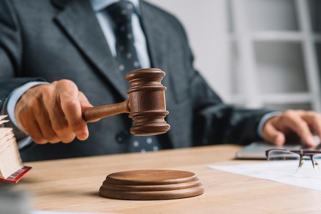 Advogado masculino do juiz que dá o veredicto batendo o martelo do malho no bloco de som Foto gratuita