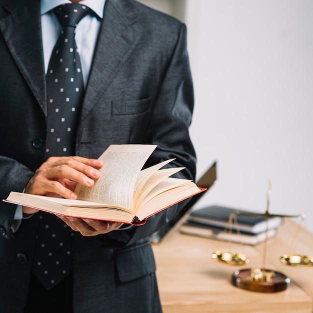 Advogado masculino, leitura, livro, ficar, frente, escrivaninha Foto gratuita