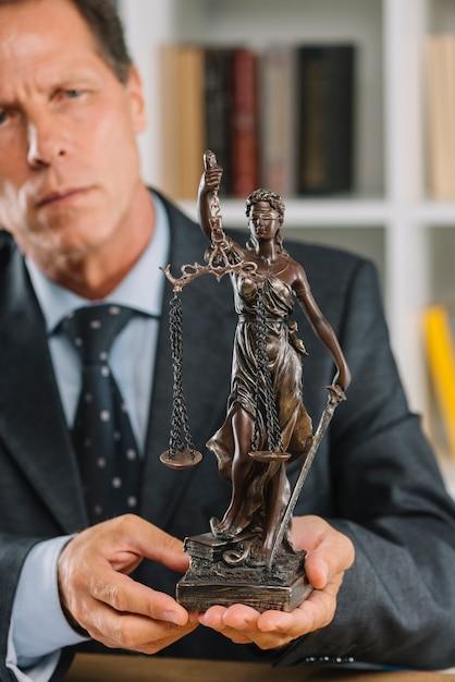 Advogado masculino maduro, segurando a estátua da justiça na mão Foto gratuita