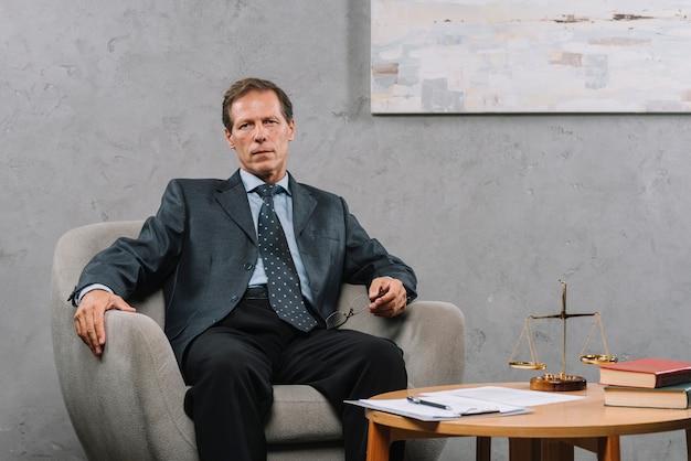 Advogado masculino maduro, sentado na poltrona no tribunal Foto gratuita