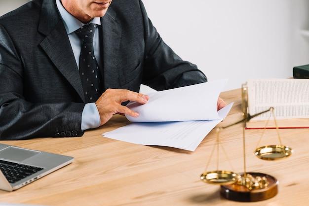 Advogado masculino maduro, virando as páginas do documento na mesa Foto gratuita