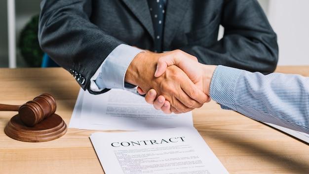 Advogado masculino que agita as mãos com o cliente sobre o papel do contrato na tabela Foto gratuita
