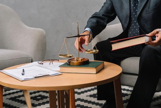 Advogado masculino segurando o livro de direito sentado no escritório Foto gratuita