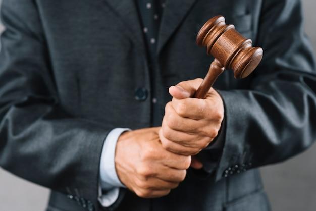 Advogado masculino, segurando o malho de madeira na mão Foto gratuita