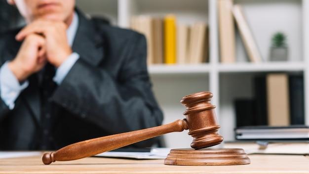 Advogado masculino sentado atrás do martelo do juiz na mesa de madeira Foto gratuita
