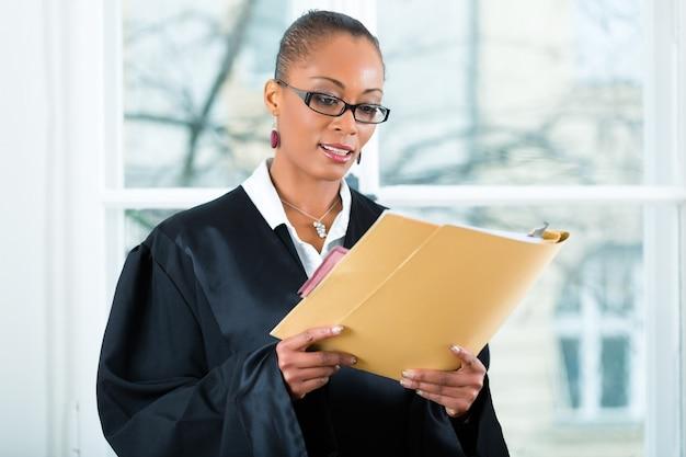 Advogado no escritório com dossiê em pé uma janela Foto Premium