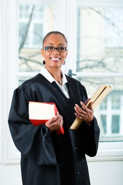 Advogado no escritório com livro de direito e dossiê Foto Premium