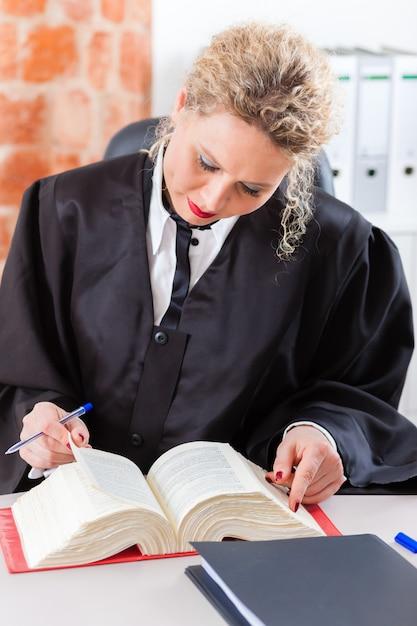 Advogado no escritório lendo livro de direito Foto Premium