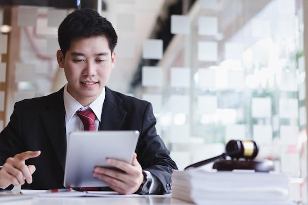 Advogados de negócios que usam o telefone celular para o cliente do contato com a escala de bronze na mesa de madeira no escritório. direito, serviços jurídicos, consultoria, consultoria, justiça. Foto Premium