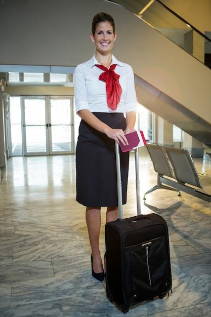Aeromoça sorridente com cartão de embarque e mala no terminal do aeroporto Foto gratuita