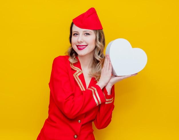 Aeromoça vestindo em uniforme vermelho com caixa de gfit feriado de forma de coração Foto Premium