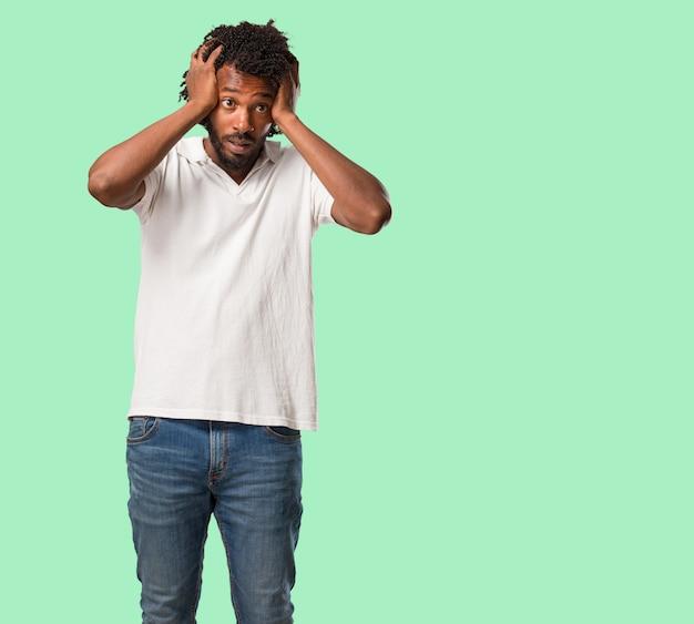 Africano-americano bonito frustrado e desesperado, irritado e triste com as mãos na cabeça Foto Premium