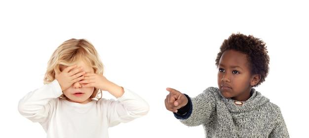 Africano criança dizendo uma ordem para seu amigo, que está cobrindo os olhos Foto Premium