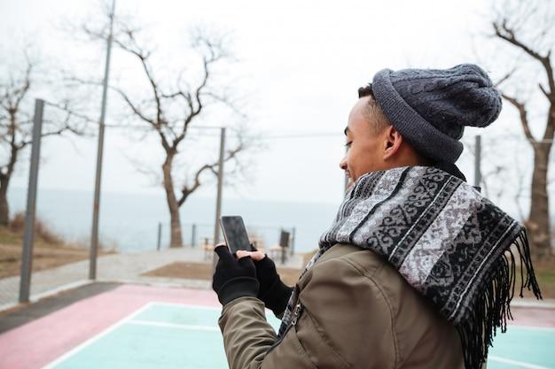 Africano jovem bonito conversando por telefone. Foto gratuita