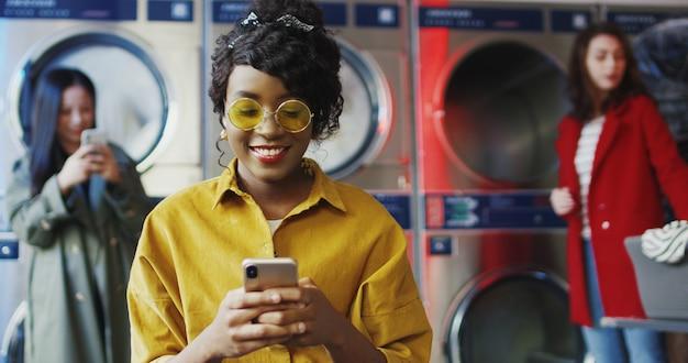Afro-americana jovem bonita e elegante garota de óculos amarelos em pé na sala de serviço de lavanderia e batendo no smartphone. mensagem de mulher no telefone enquanto aguarda a roupa ser lavada. Foto Premium