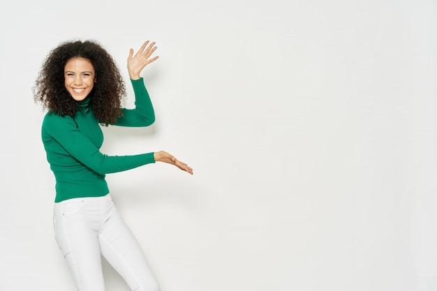 Afro-americano da mulher que mostra um produto no copyspace Foto Premium