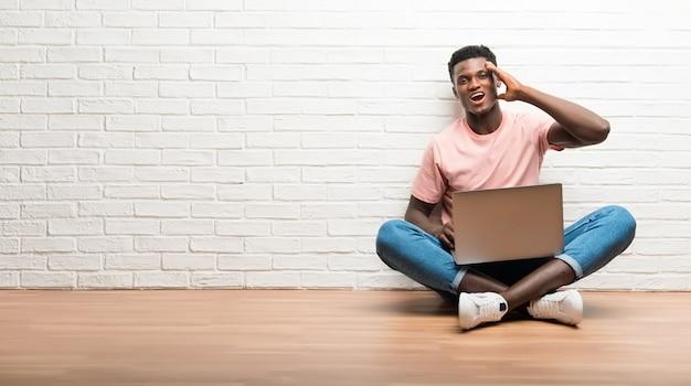 Afro americano homem sentado no chão com seu laptop com a intenção de perceber a solução Foto Premium