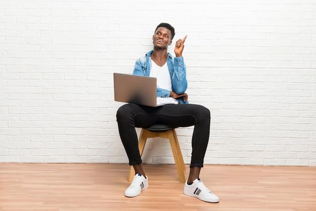Afro americano homem trabalhando com seu laptop apontando com o dedo indicador uma ótima idéia Foto Premium