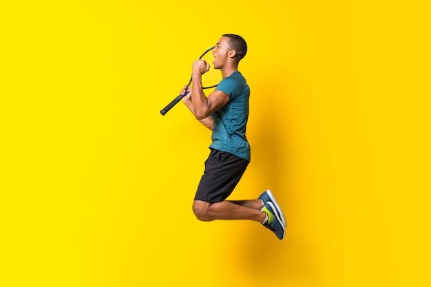 Afro americano jogador de tênis homem sobre amarelo isolado Foto Premium