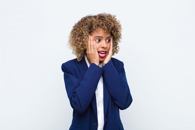 Afro-americano jovem, sentindo-se feliz, animado e surpreso, olhando para o lado com as duas mãos no rosto contra a parede plana Foto Premium