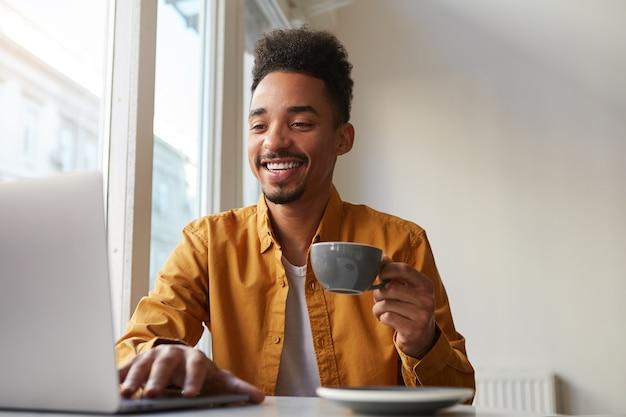 Afro-americano sentado à mesa em um café e trabalhando no laptop, veste uma camisa amarela, bebe um café aromático, se comunica com sua irmã que está longe de outro país, gosta do trabalho Foto gratuita