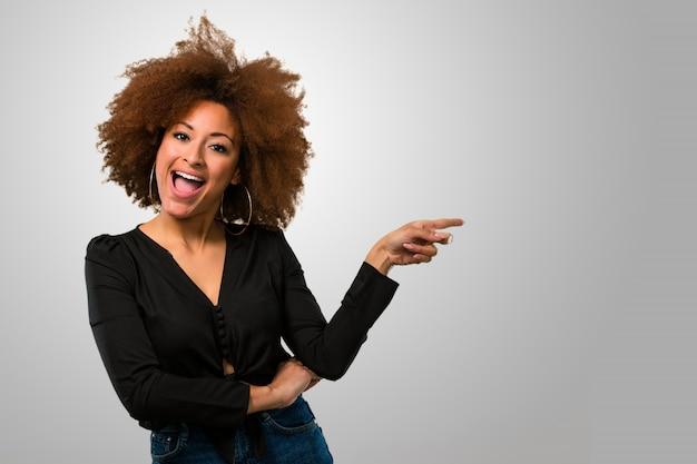 Afro mulher apontando para o lado Foto Premium