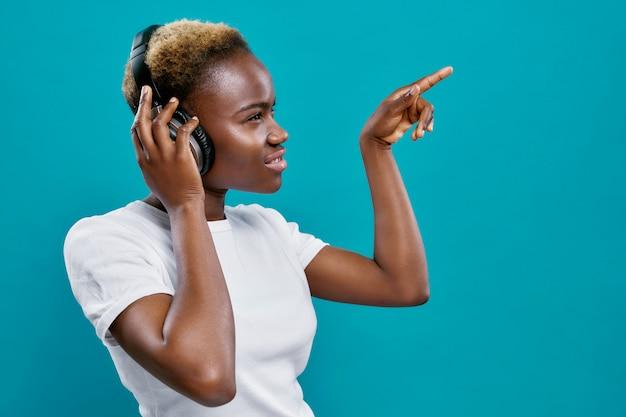 Afro mulher com cabelo curto, ouvindo música com fones de ouvido. Foto Premium