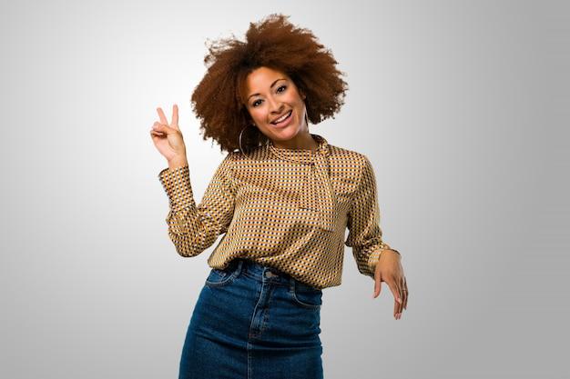 Afro mulher fazendo um sinal de vitória Foto Premium