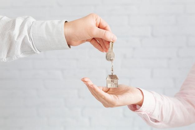 Agente da casa dando chaves ao cliente Foto gratuita