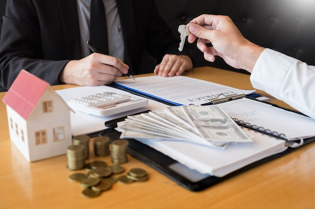 Agente de desenvolvimento imobiliário e assinar no documento dando as chaves da casa nova Foto Premium